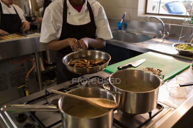 Section du milieu du chef préparant la nourriture dans la cuisine au restaurant — Photo de stock