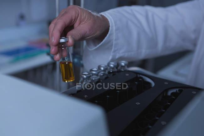 Gros plan d'un scientifique masculin plaçant une bouteille chimique sur une machine — Photo de stock