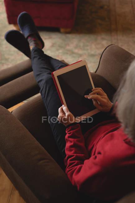 Donna anziana che utilizza tablet digitale in soggiorno a casa — Foto stock