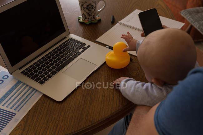 Utilizando el teléfono móvil al niño jugando con el juguete en la casa del padre - foto de stock