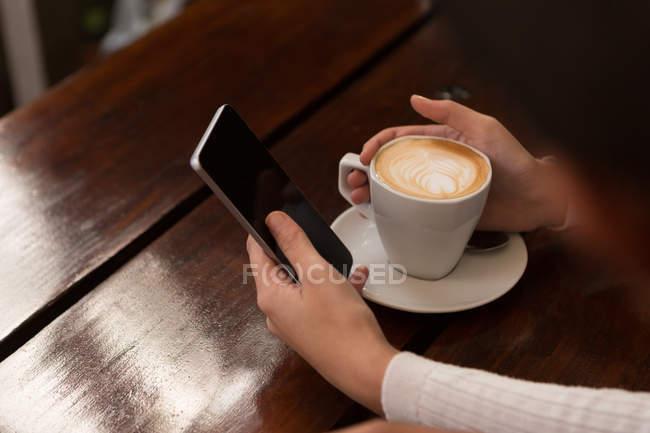 Закри жінка, що використання мобільного телефону у кафе — стокове фото