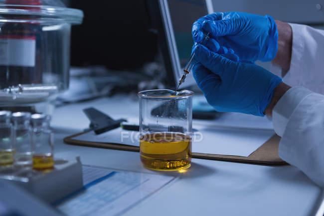 Primer plano del científico masculino que experimenta en laboratorio - foto de stock