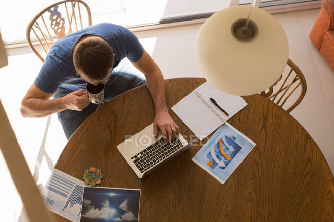 Man using laptop while having coffee at home — Stock Photo