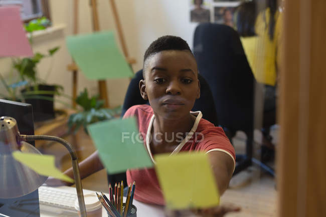 Attentive female executive looking at sticky notes in office — Stock Photo