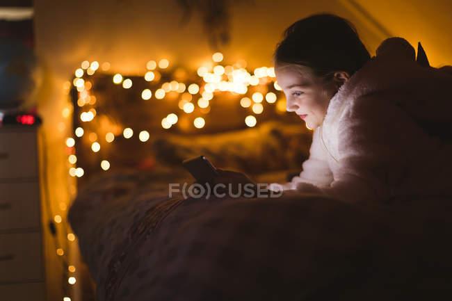 Ragazza sorridente utilizzando tablet digitale contro le luci di Natale — Foto stock