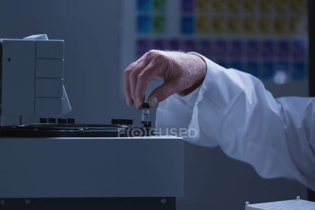 Male scientist placing chemical tube glass bottle on a machine in laboratory — Stock Photo