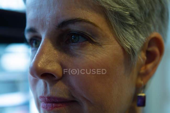 Primer plano de la clínica optometrista mujer mayor reflexiva - foto de stock