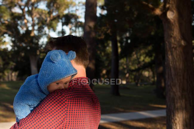 Pai segurando seu menino no parque em um dia ensolarado — Fotografia de Stock