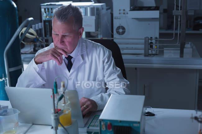 Вдумчивый ученый-мужчина использует ноутбук в лаборатории — стоковое фото