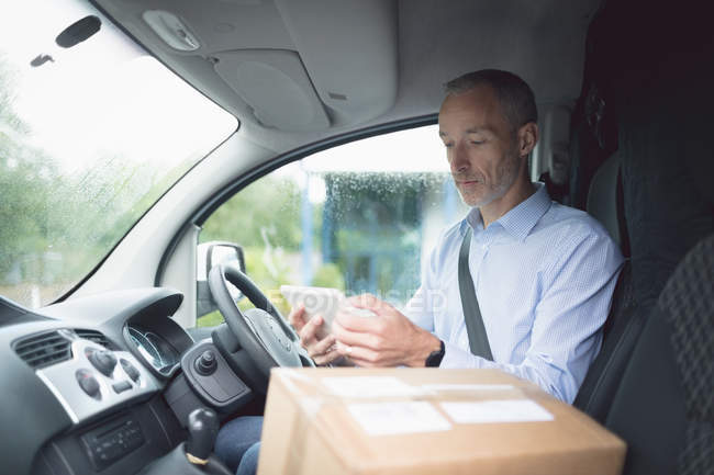 Side view of delivery man using digital tablet in delivery van — Stock Photo