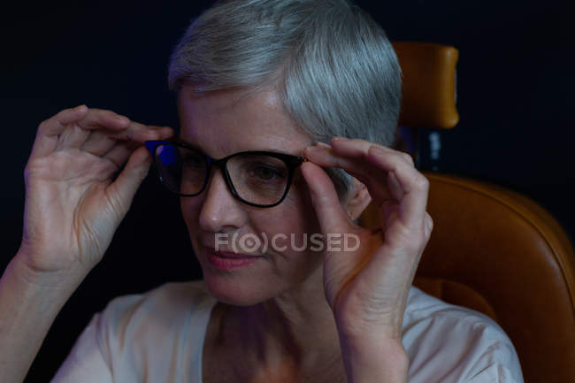 Close-up of senior woman adjusting eyeglasses in clinic — Stock Photo