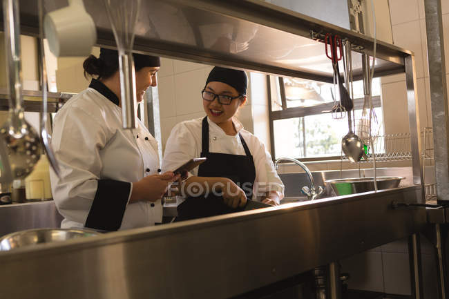 Two female chefs interacting with each other in kitchen at restaurant — Stock Photo