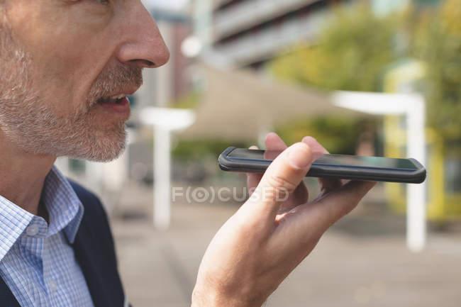 Primer plano del hombre de negocios hablando por teléfono móvil en la ciudad - foto de stock