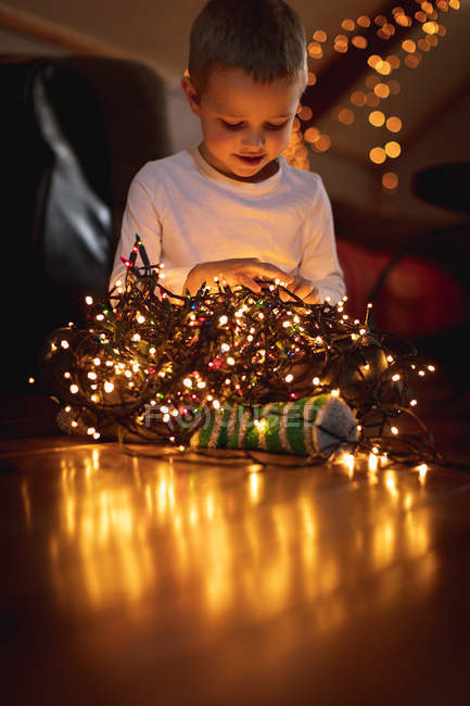 Curious boy looking at illuminated fairy lights at home — Stock Photo