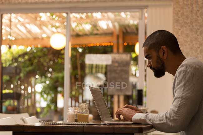 Side view of man using laptop in cafe — Stock Photo