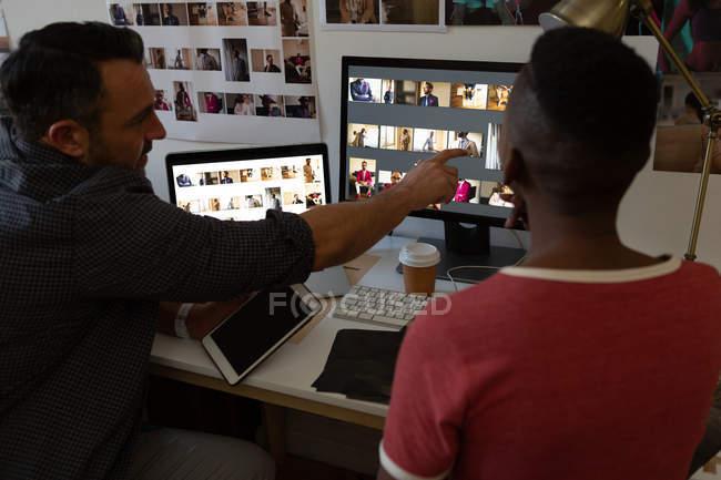 Colegas de negócios discutindo sobre um computador na mesa no escritório — Fotografia de Stock