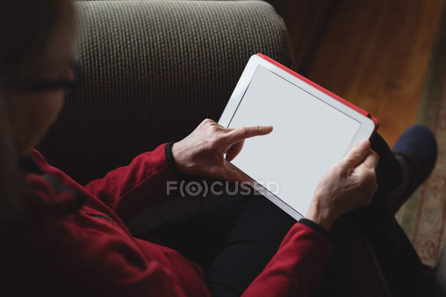 Senior woman using digital tablet in living room at home — Stock Photo