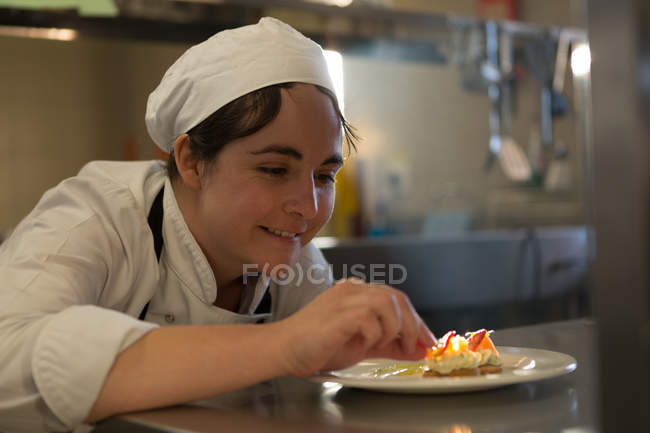 Female chef garnishing food on plate in kitchen — Stock Photo