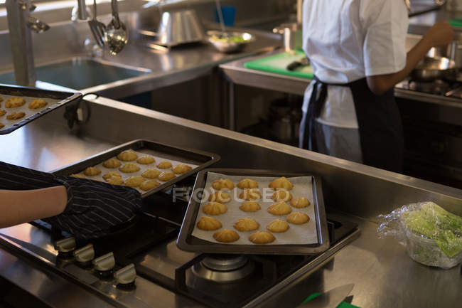 Chef holding tray of cookies in kitchen at home — Stock Photo
