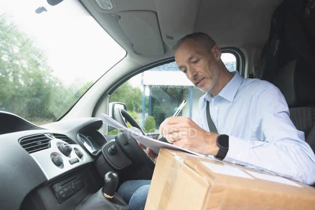 Вид курьера, пишущего на бумаге в фургоне — стоковое фото
