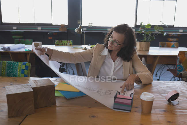 Dirigeante travaillant sur le plan à la table au bureau — Photo de stock