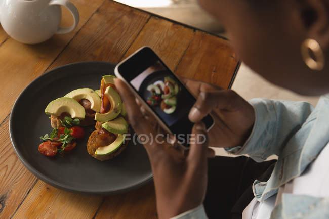 Woman taking picture of food in cafe — Stock Photo