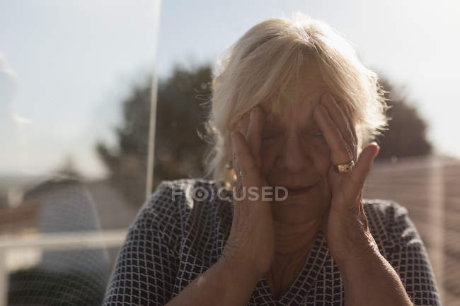 Senior woman suffering from headache in the garden — Stock Photo