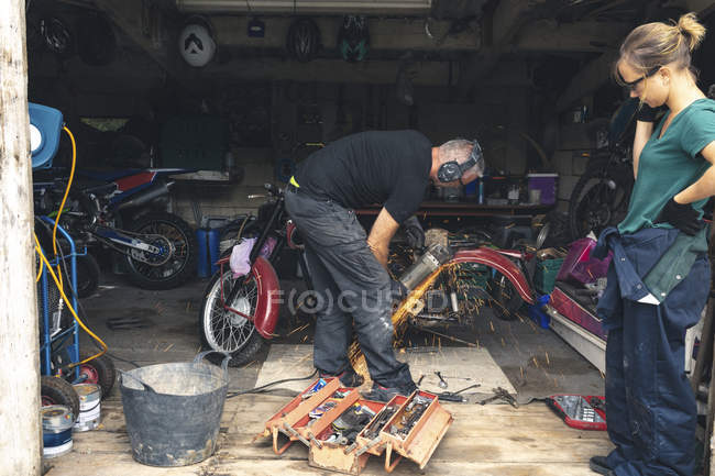 Mechanic using grinder in repair garage — Stock Photo