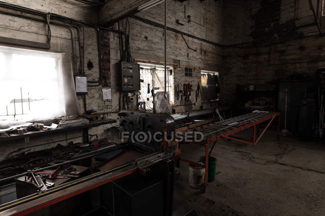 Metal tools and equipment in empty workshop — Stock Photo