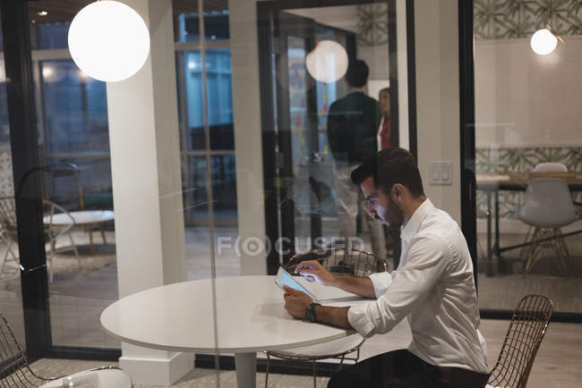 Concentrated businessman using digital tablet in the cabin at office — Stock Photo
