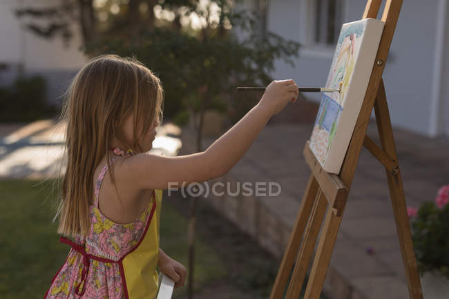 Side view of girl painting on canvas in the garden — Stock Photo