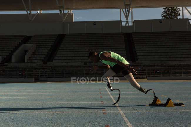 Side view of disabled athlete running on a running track — Stock Photo