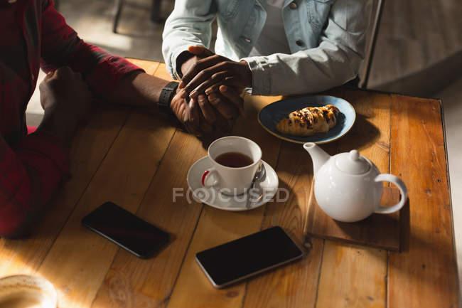 Розділ середині пара, тримаючись за руки кафе круасани — стокове фото