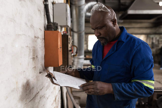 Attentive blacksmith looking on clipboard in workshop — Stock Photo