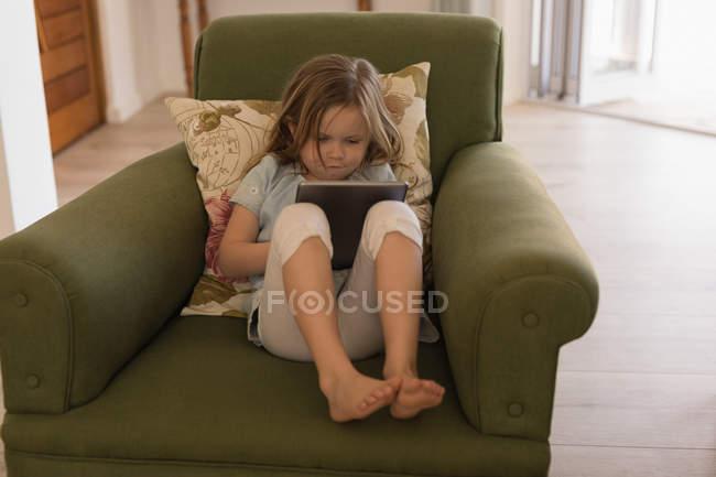 Девушка с использованием цифрового планшета в гостиной дома — стоковое фото
