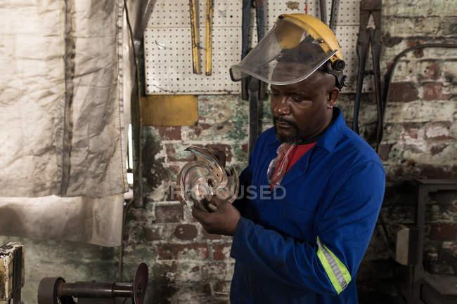 Fabbro maschio controllo lama di metallo in officina — Foto stock