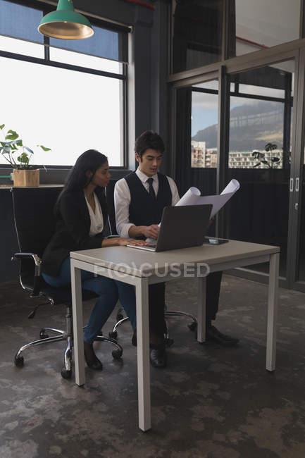 Imprimer des cadres discutant sur bleu tout en utilisant le portable de bureau — Photo de stock
