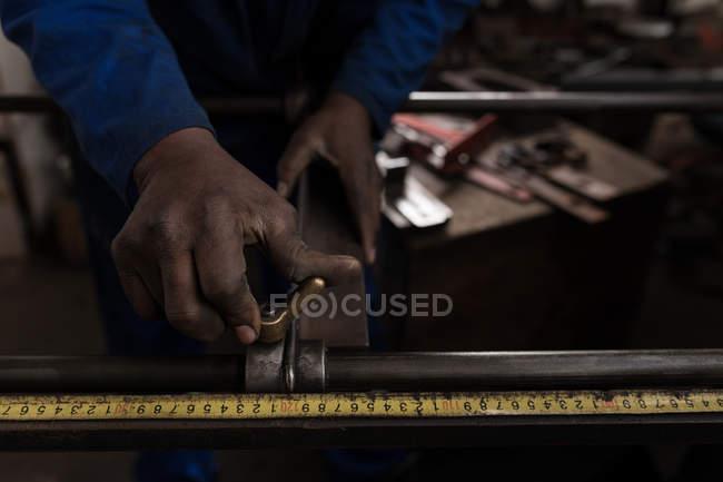 Close-up of blacksmith measuring metal rod in workshop — Stock Photo