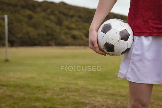 Розділ середині футболіста, стоячи з футбольним м'ячем у сфері — стокове фото