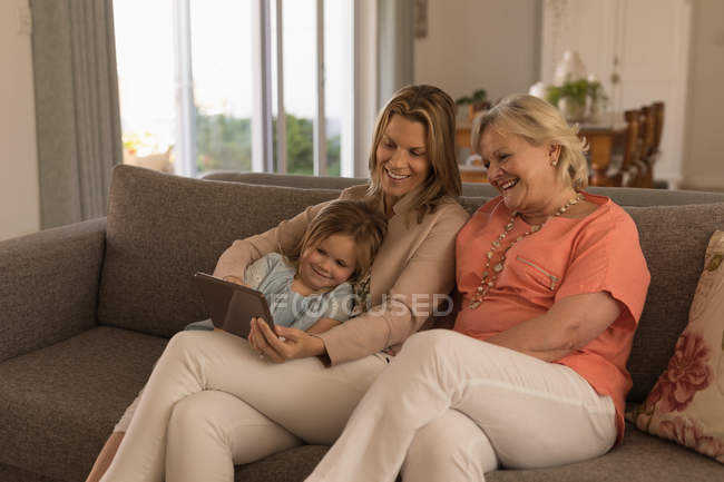 Multi-generation family using digital tablet in living room at home — Stock Photo