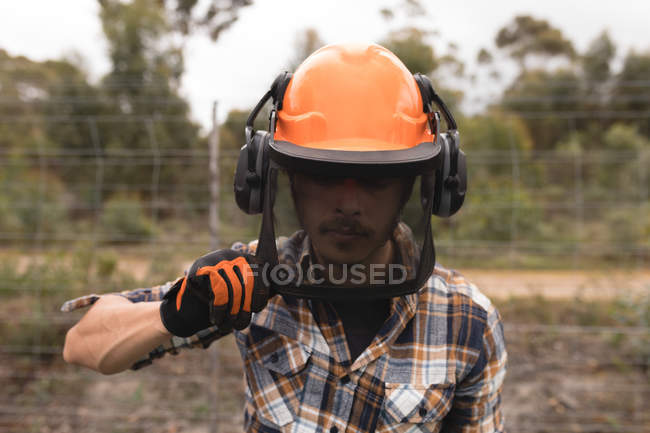 Close-up of lumberjack in hardhat at forest — Stock Photo