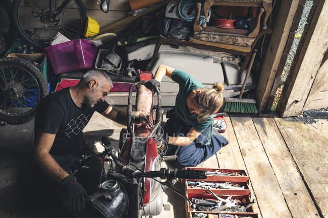 Висока кут зору механік ремонту мотоцикл в гаражі — стокове фото
