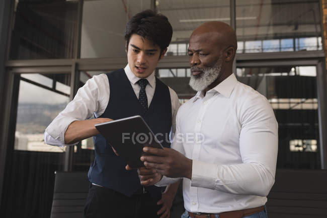 Executives discussing over digital tablet in office — Stock Photo
