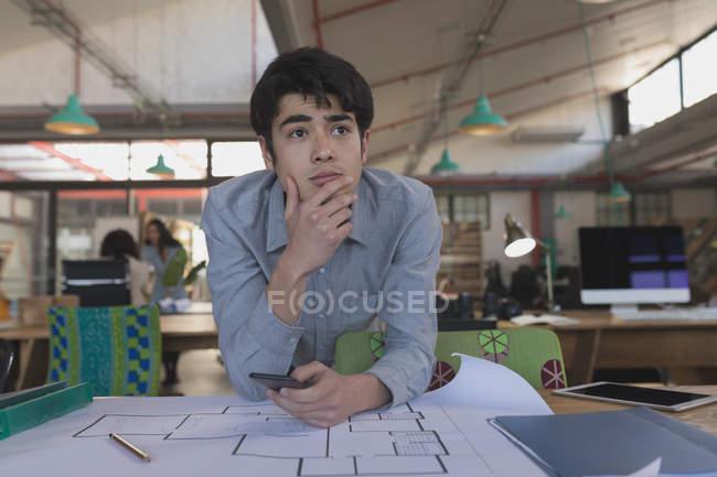 Вдумчивый мужчина, использующий мобильный телефон в офисе — стоковое фото