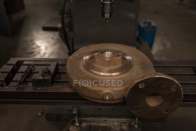 Close-up press drill and metal piece in workshop — Stock Photo