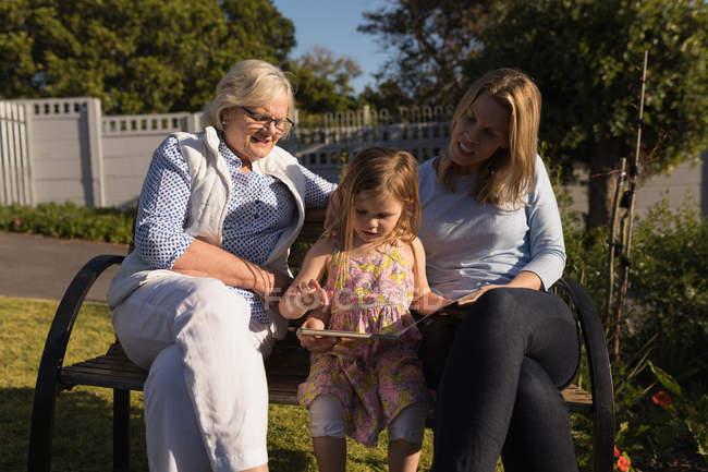 Família de várias gerações, olhando o álbum de fotos no jardim em um dia ensolarado — Fotografia de Stock