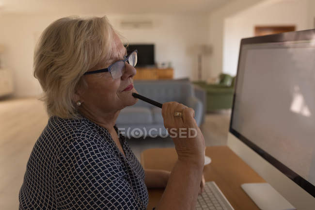 Senior woman working on computer at home — Stock Photo