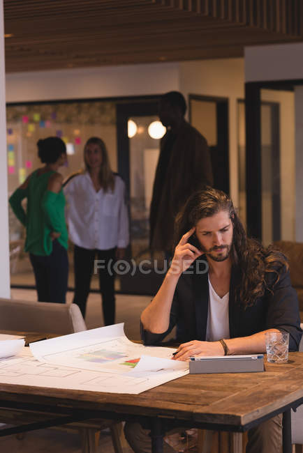 Thoughtful businessman working on blueprints in the office — Stock Photo
