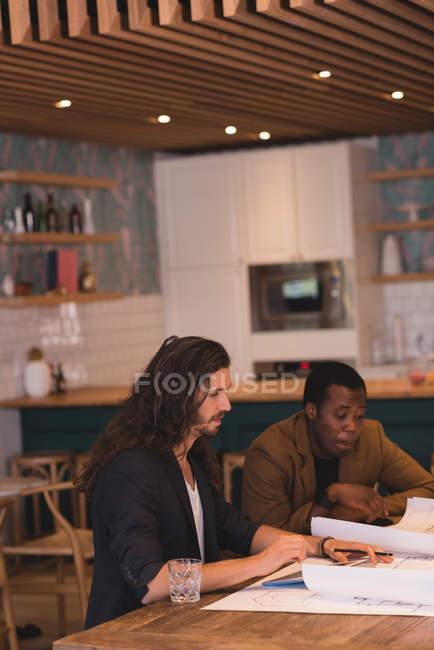 Два предпринимателя, обсуждая чертежи в офисе — стоковое фото