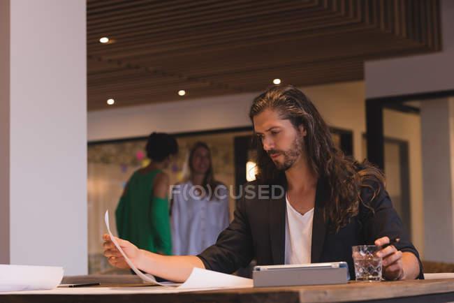 Concentré d'affaires vérifiant les esquisses sur papier au bureau — Photo de stock
